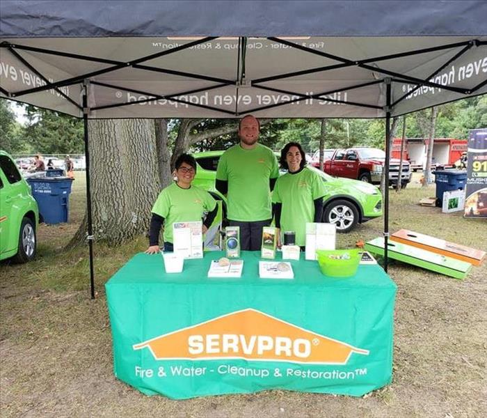 SERVPRO of Muskegon marketing team posing behind their booth at Sportsmen for Youth-Youth Day.